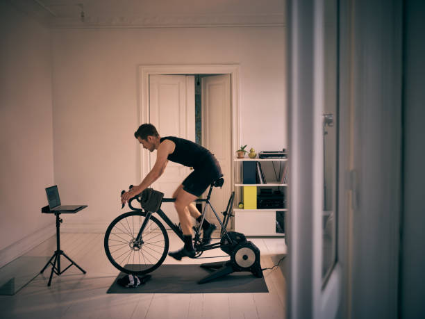 No gym, no problem Shot of a young man working out on an exercise bike at home exercise bike stock pictures, royalty-free photos & images