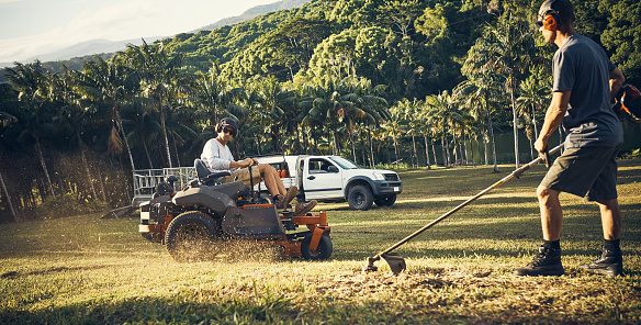 Shot of two landscapers trimming a lawn in a park