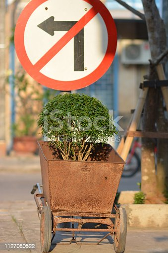 No left turn and small rusty cart used as plant pot, image taken in Savannakhet,  Laos