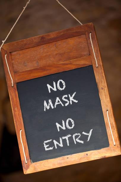Sin Máscara Sin Entrada Coronavirus COVID-19 pizarra de madera o cartel de menú de pizarra colgando en una tienda minorista, restaurante o cafetería - foto de stock