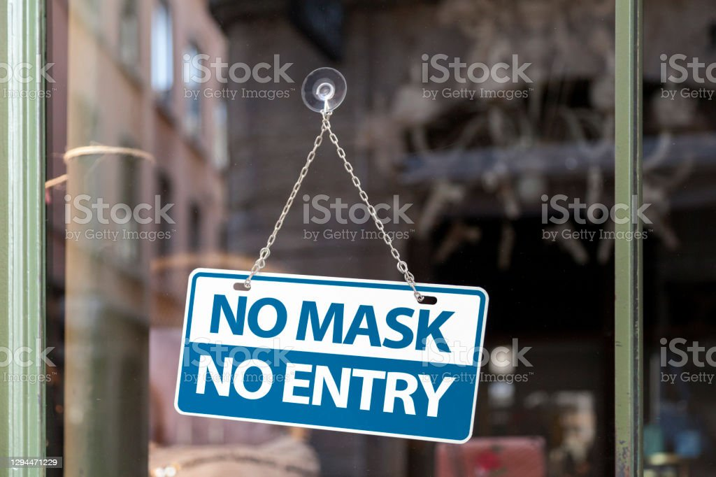 """No mask No entry Close-up on a blue and white sign in a window with written in it """"No mask No entry"""". Bar - Drink Establishment Stock Photo"""