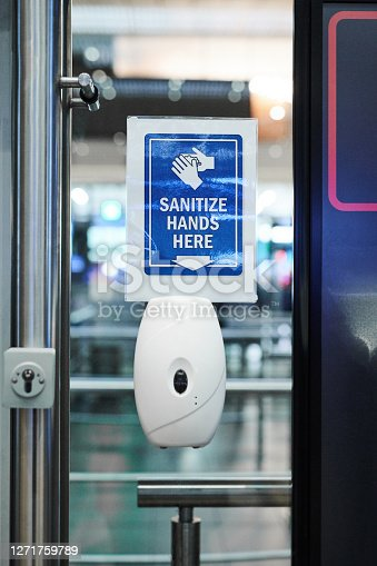 Shot of an automatic hand sanitiser dispenser on a door in an airport