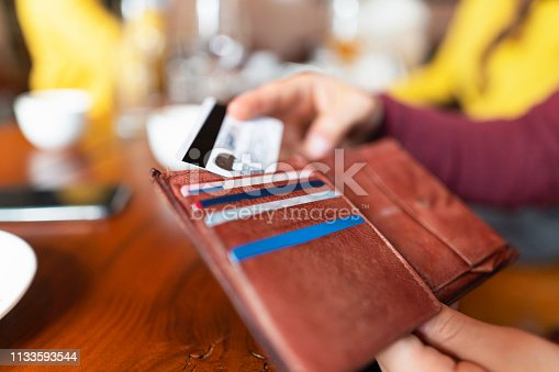 Close - up shot of unrecognizable man getting a credit card from his wallet to pay the drink at the bar.