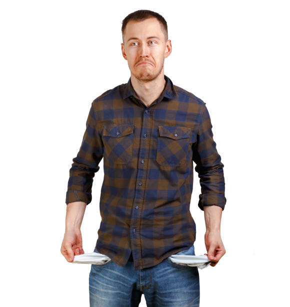 no money concept. young man in a checkered shirt showing empty pockets, sad unhappy face expression. isolated on white background - pocket stock photos and pictures