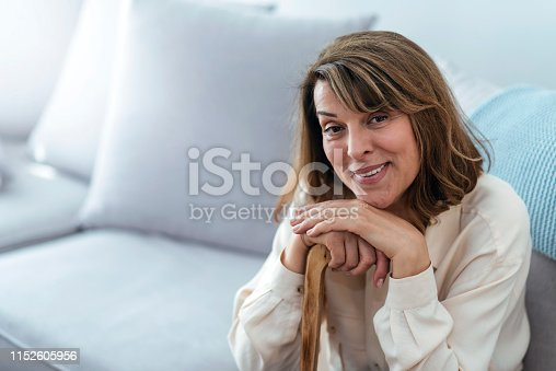 A retired woman with her wooden walking stick at home. Happy senior woman relaxing at home holding cane and looking at the camera with a toothy smile. Smiling grandmother sitting on the couch during the day. Portrait of a beautiful smiling senior woman with walking cane on the light background at home.