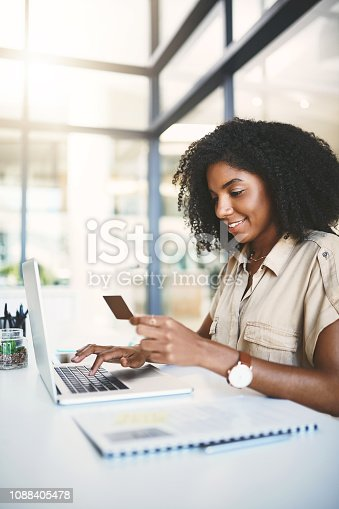 Shot of a young businesswoman using a credit card and laptop in a modern office