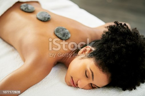 Shot of an attractive young woman getting a hot stone massage at a spa
