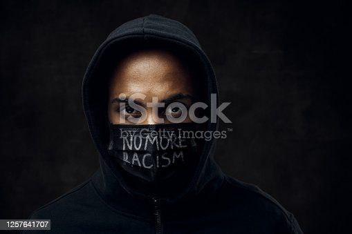 Afroamerican man wearing hoodie and black facial mask. Anti-racism concept.