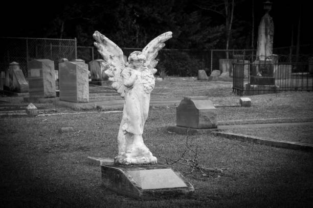 no name spooky grave headstone angel statue in a creepy old cemetery in black and white stock photo