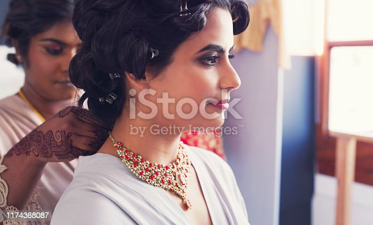 Shot of a beautiful young woman getting her necklace put on by her bridesmaid on her wedding day