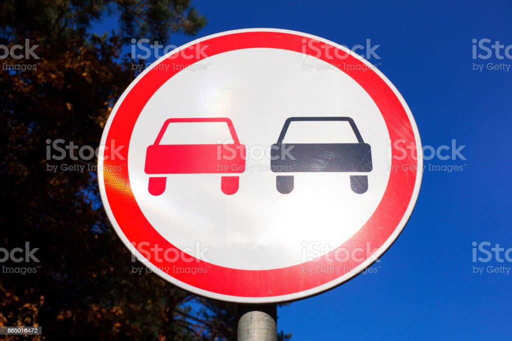 No Overtaking road sign against blue sky and tree. stock photo