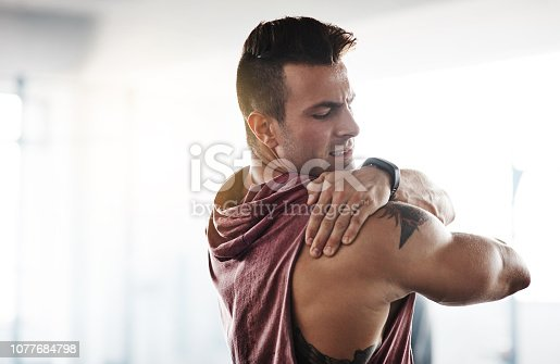 Cropped shot of a handsome young man stretching at the gym