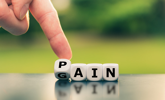istock No pain no gain. Hand turns a dice and changes the word