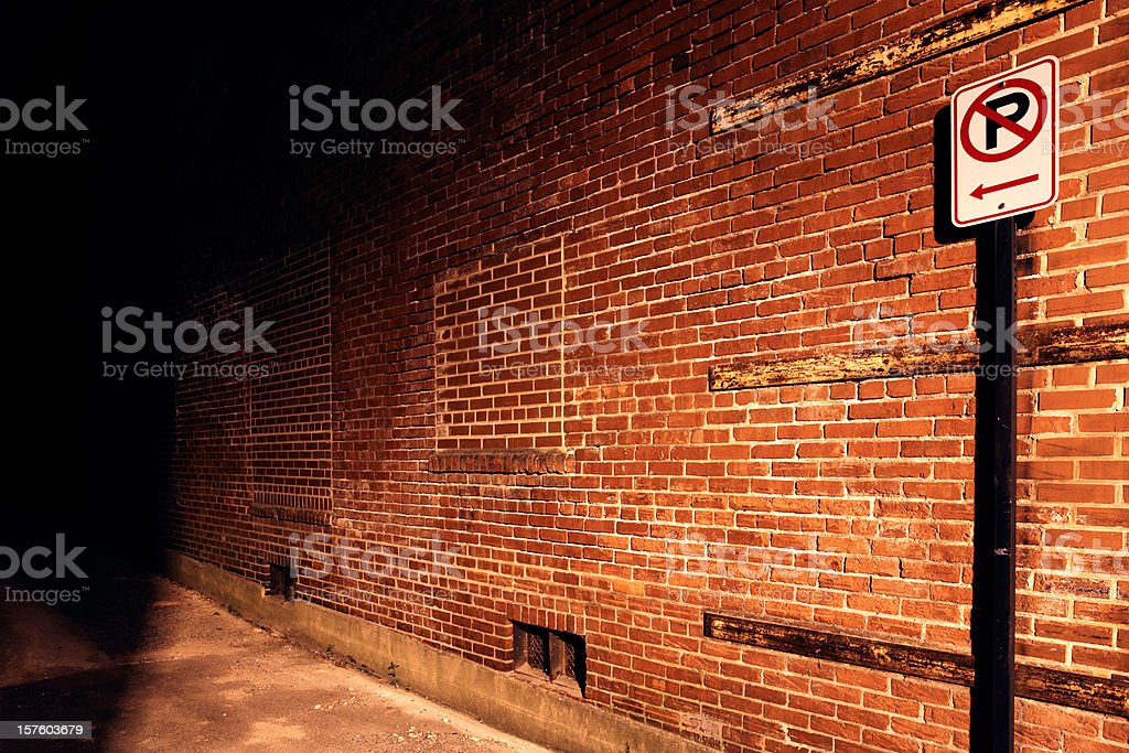 No parking sign leading to dark alley stock photo