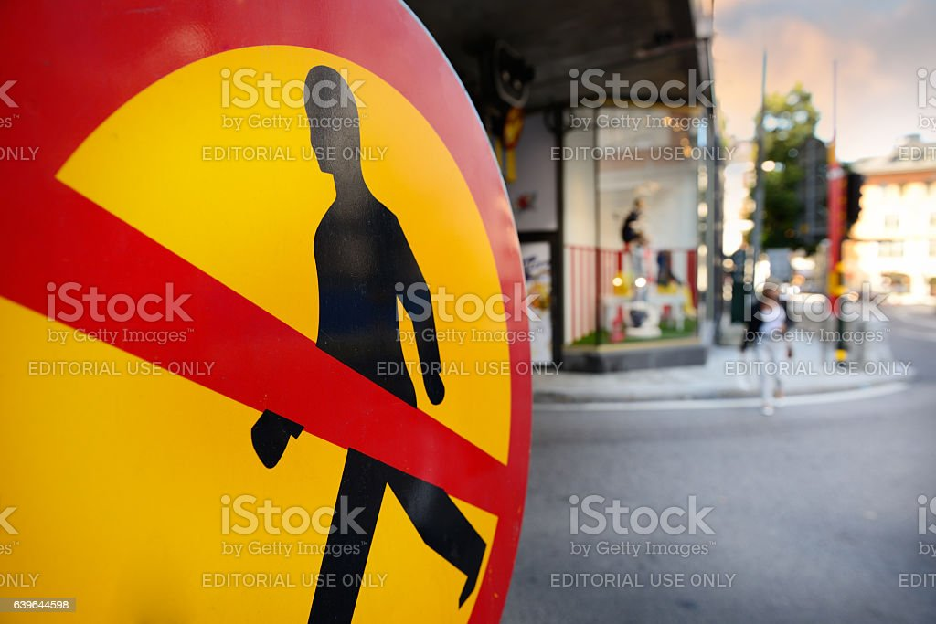 No pedestrians sign, pedestrian in background anyway stock photo