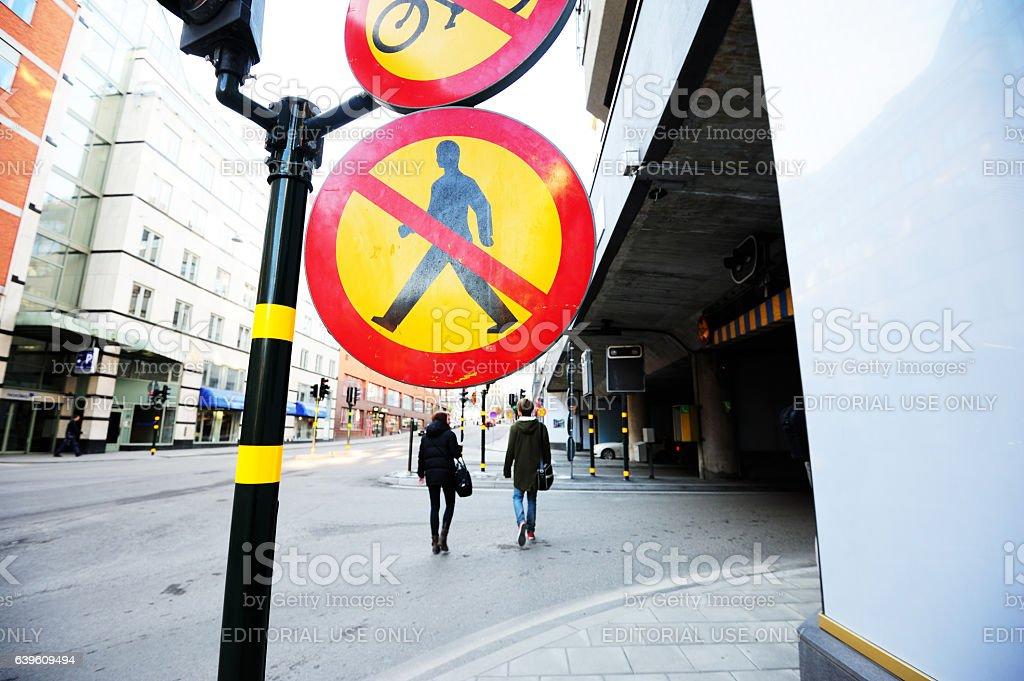 No pedestrians sign, pedestrians in background anyway stock photo
