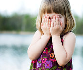 Color image of a Little girl covering her eyes.