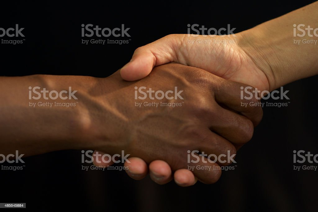 No Racism - Indian man and Italian Woman shakeing hands stock photo