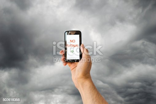hand with a phone searching for signal with a stormy sky