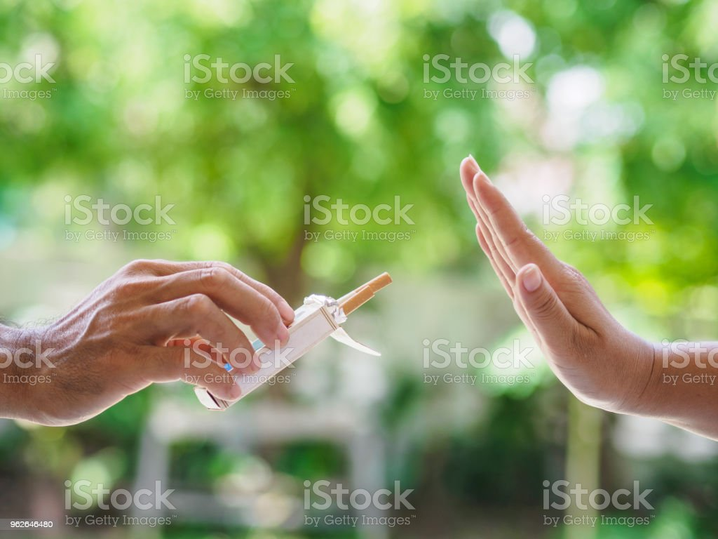 No smoking. Close up of male hands holding cigarettes and proposing it to person. The human arm is gesturing with refusal on bokeh background. stock photo
