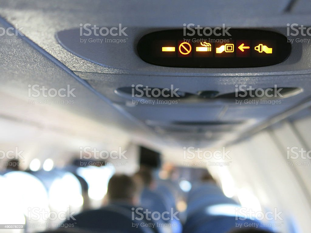 No Smoking Fasten Seatbelt Sign with Passengers on Airplane stock photo