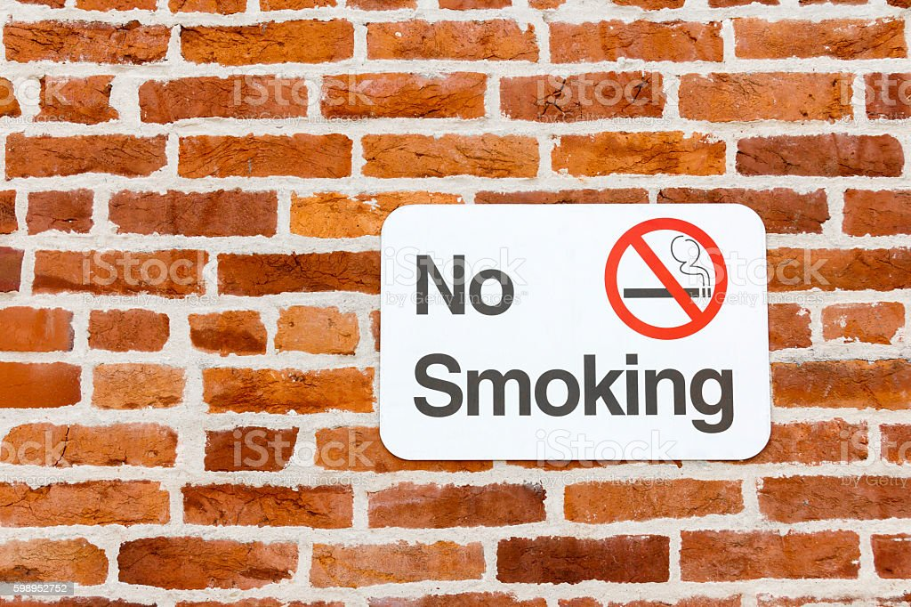 No Smoking Sign On a Red Brick Wall stock photo