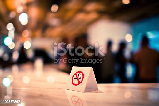 In a Tokyo bar, a no smoking sign on the counter.