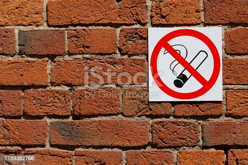 istock No Smoking Sign with cigarette symbol on red brick wall. Copy space 1159357766