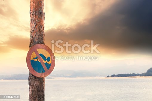istock No swimming sign in front of dangerous lake, dramatic clouds behind 926537406