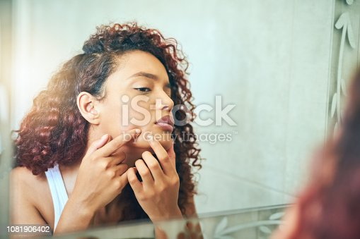 Cropped shot of a young woman squeezing a pimple on her face