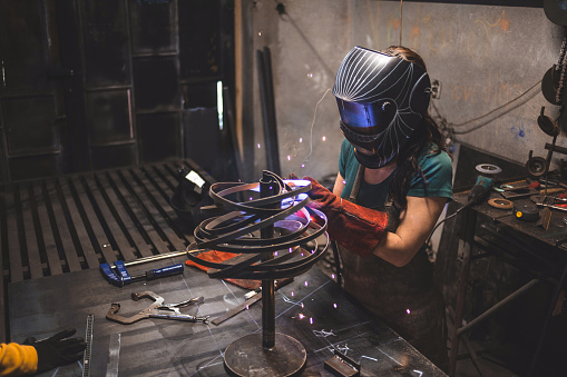 Gorgeous young girl designing a sculpture of metal, and making it.