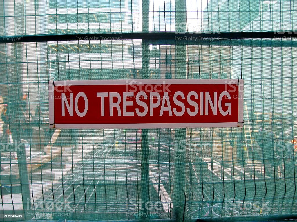 No trespassing as warning message on metal grid wall stock photo