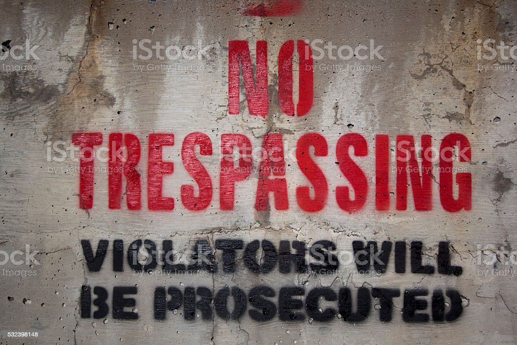 No trespassing on a cement wall stock photo