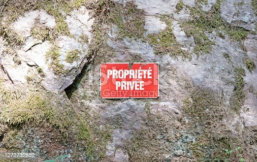 No trespassing private property red sign on a stone wall