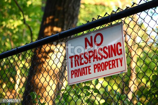 A close-up image of a 'No trespassing - private property' sign hanging on a fence with green trees on the background