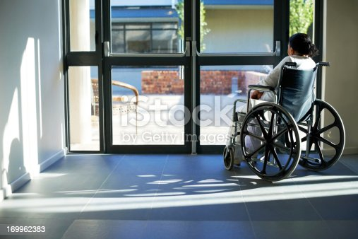 An old woman sitting in a wheelchair at the the door of an institution