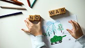 No war text on cubes, child painting military situation, political problems