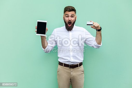 istock No way! Online shopping. Businessman holding hands credit card and tablet and looking at with shocked face. Indoor, studio shot. Isolated on light green background 838859372