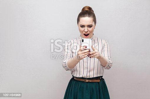 640046924 istock photo No way! Portrait of shocked attractive blogger young woman wearing in striped shirt standing, using smartphone and watching video with amazed face. 1091494968