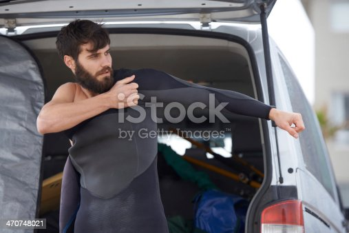 A young man putting on his wetsuit before a surf