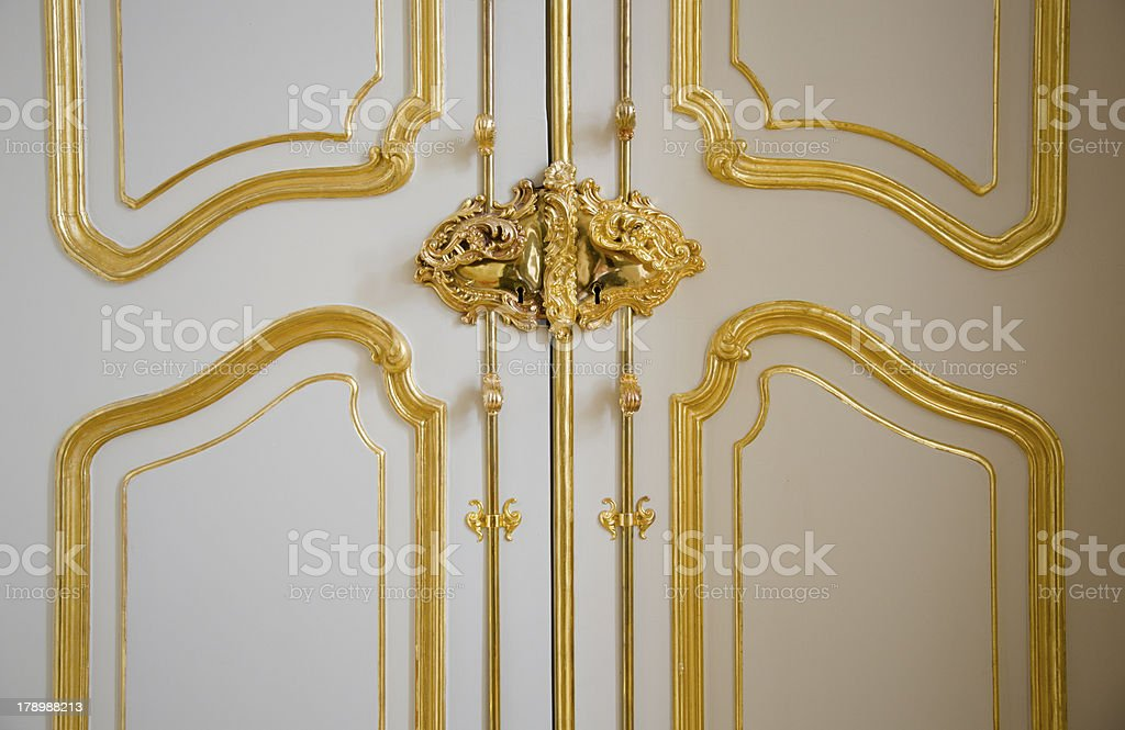 Noble castle door with gilded ornaments stock photo