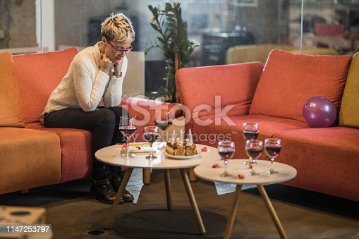 Young woman feeling sad while sitting alone on her Birthday party in the office.