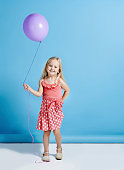 Shot of a cute little girl holding a balloon over a blue background