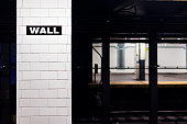 New York City, USA - October 30, 2017: Nobody in underground transit empty large platform in NYC Subway Station, railroad tracks, Wall street sign in downtown isolated on tiled column