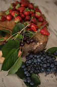 High angle view of a rustic wooden log placed on top of the table with several sour cherries and plenty of beautiful strawberries on top of it, while few dozens of blueberries are placed directly next to this assembly.