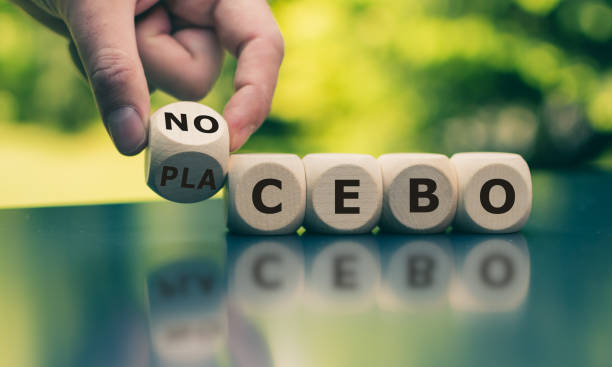 """Nocebo or placebo? Hand turns a cube and changes the word """"placebo"""" to """"nocebo"""", or vice versa. stock photo"""