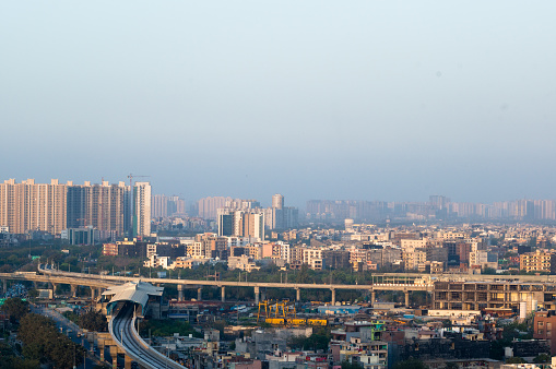 Noida Delhi cityscape with skyscrapers, small houses and metro in the distance. Shows the amazing infrastructure in the city and transport options available