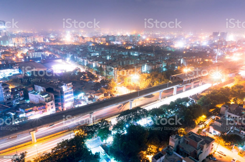 Noida metro station at night against the cityscape stock photo