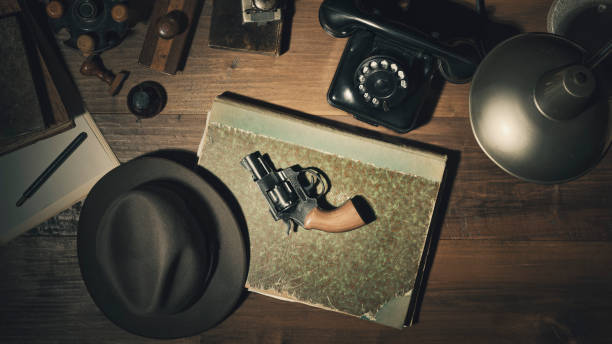 Noir 1950s style detective desktop with revolver Noir 1950s style detective vintage desktop with revolver, fedora hat and telephone, flat lay gangster stock pictures, royalty-free photos & images