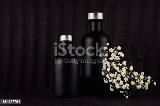 847096968 istock photo Noir exquisite home decor with blank black cosmetics bottles, white small flowers on dark wood board, mock up. 864357794